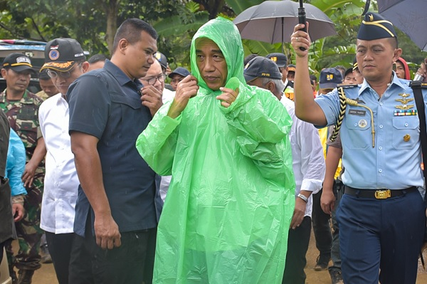 Saat Presiden Kenakan Jas Hujan Pemberian Warga di Sukajaya